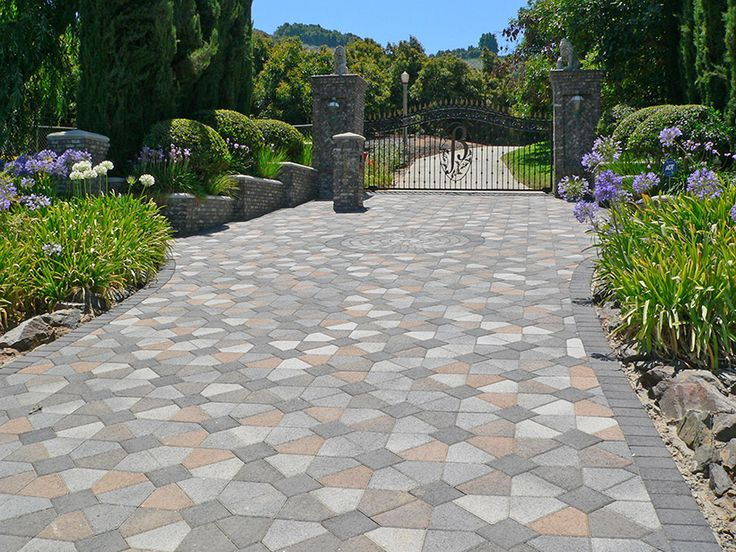 Grand entrance paver driveway crafted with multi-color pavers in a symmetrical…