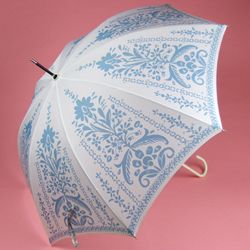 Ivory umbrella with a pastel slate blue stenciled floral design finished with a white hook handle.