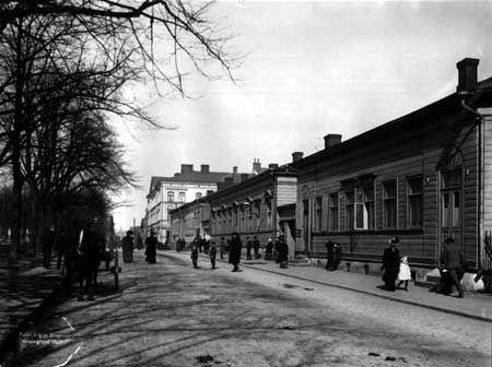 Itäinen Heikinkatu, nykyinen Mannerheimintie, Aleksanterinkadun ja Kaivokadun välillä 1907. Etummaiset puutalot katosivat, kun Uutta ylioppilastaloa rakennettiin. Talon vihkiäisiä vietettiin marraskuussa 1910. Kuva: Signe Brander.
