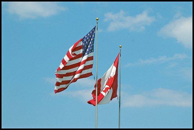 On both sides of the border, the flags of U.S. and Canada are displayed together in public spaces.