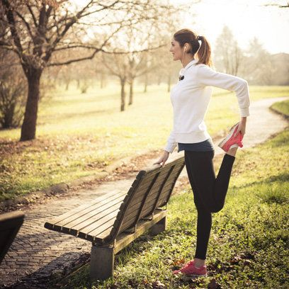 Woman stretching next to bench in park | Outdoor Fitness | Health & Self | redonline.co.uk