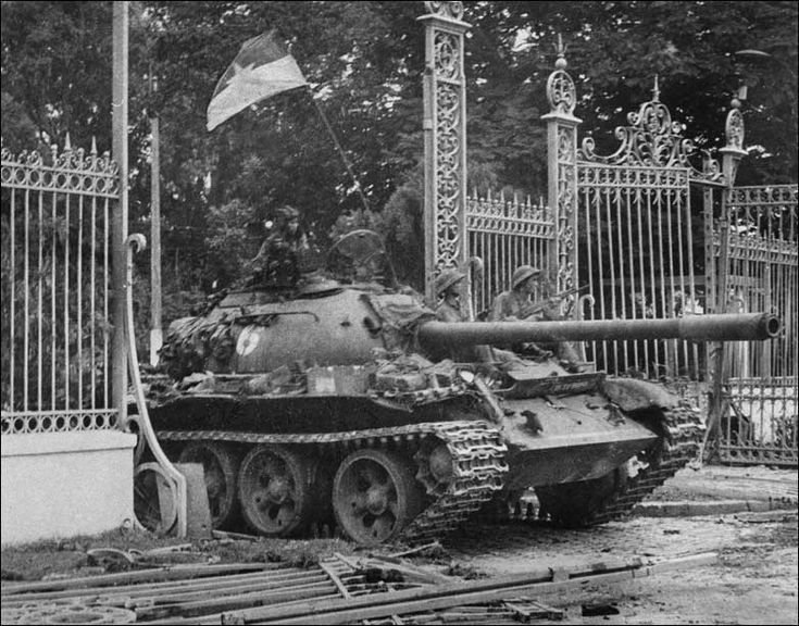Perched on a tank, soldiers of the North Vietnamese Army (NVA) go through the gates of the South Vietnamese presidential palace, 30 April 1975