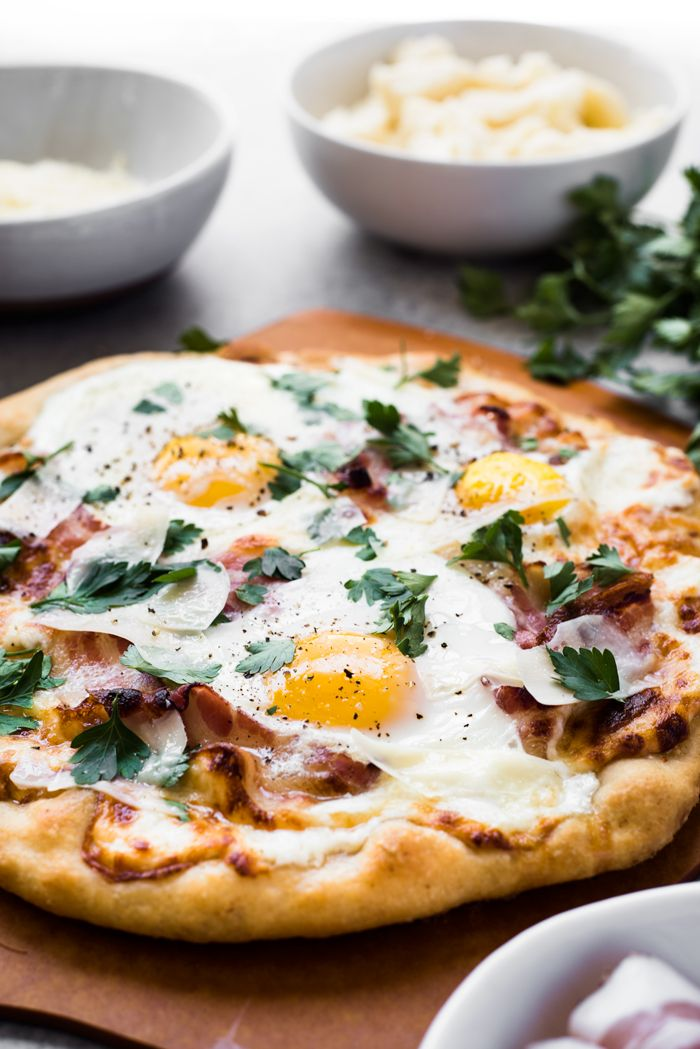 Roasted garlic, crispy pancetta, creamy sunny-side up eggs, and ooey-gooey cheese - makes this Pizza Carbonara irresistible!