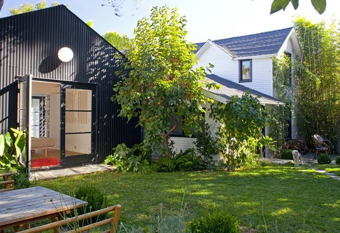 The original white farmhouse and new pavilion clad in black corrugated metal.