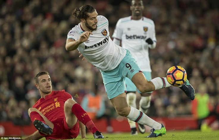 Andy Carroll (right) battles with Liverpool captain Henderson after coming on against his ...