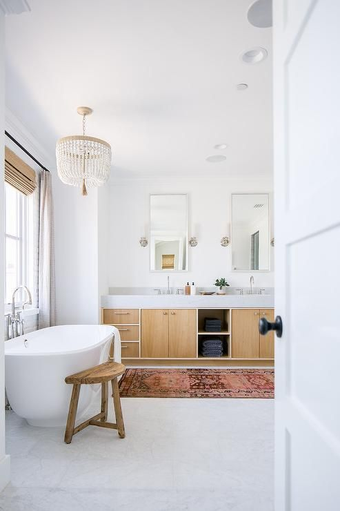 A Ro Sham Beaux Malibu Chandelier hangs over an oval freestanding bathtub paired with a polished nickel floor mount tub filler fixed to marble floor tiles beneath a window covered with a bamboo roman shade layered behind gray curtains.