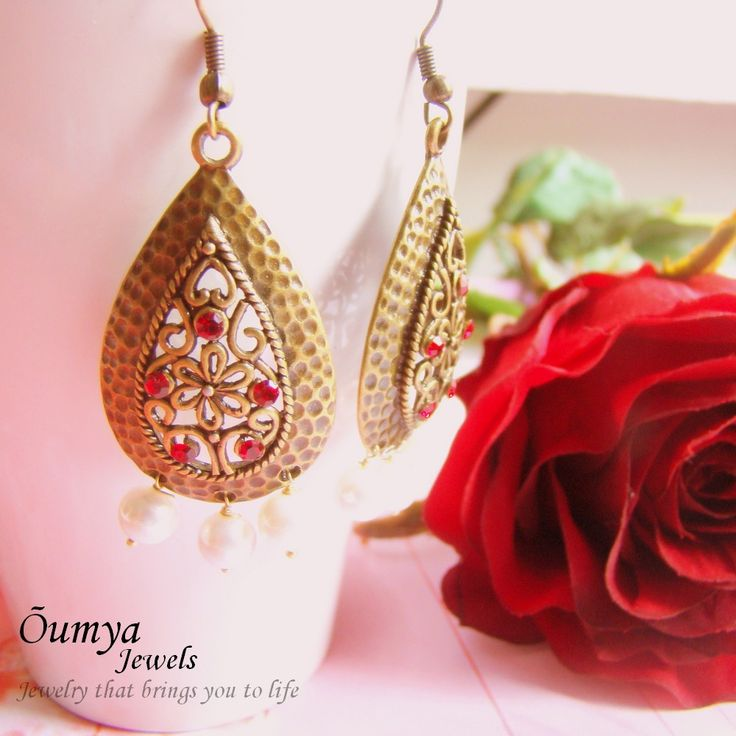 Red rhinestone studs adorn these antique brass drop shaped pendant earrings. The glass pearl has a brilliant shine that uplifts your natural beauty instantly