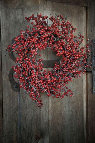 Pour changer de la traditionnelle couronne de Noël en branchages de sapin ou en pommes de pin, on habille sa porte d'entrée de baies rouge.