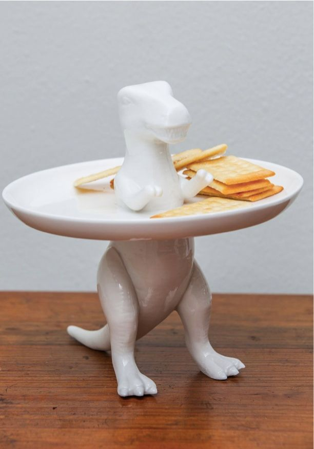 """"""" A T-Rex figurine stands right through the center of this piece's attached white plate for a touch of quirkiness that transcends time. """""""