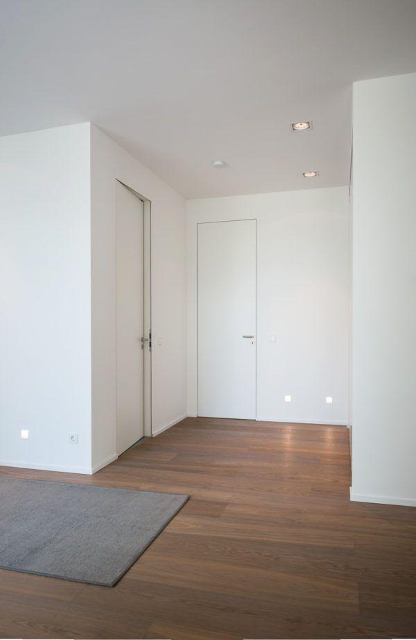 Wandbündige Reverse-Türen in zargenloser Optik. Weißes Türblatt flächenbündig.