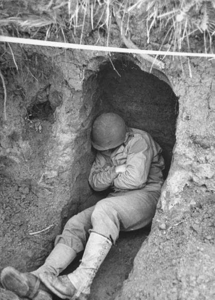 American soldier sleeping in a foxhole after a march through rugged mountain…