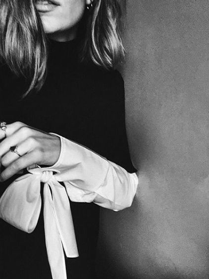 a black sweater layered over a long white blouse with bow tie sleeves peeking out. yessss