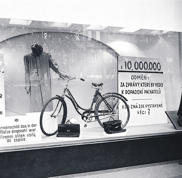 """Window of Baťa shop in Wenceslas Square, Prague, where the Nazis after the assassination exposed the personal belongings of assassins. Inscription on the right: """"10,000.000 koruns of rewarding for news leading to capture of the assassins. Who knows belongings displayed here?"""""""