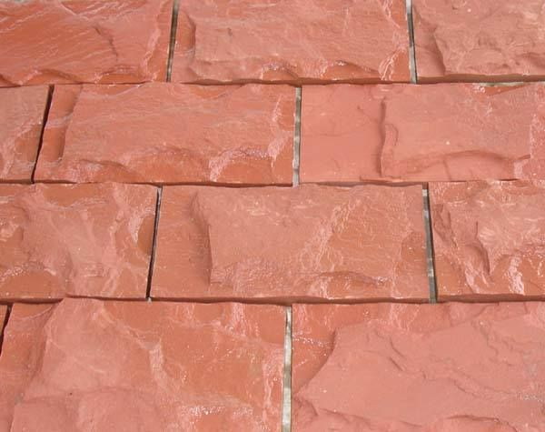 Stonemart, the leading natural stone exporter in india supplies Dholpur red sandstone wall cladding with rock face surface finish.