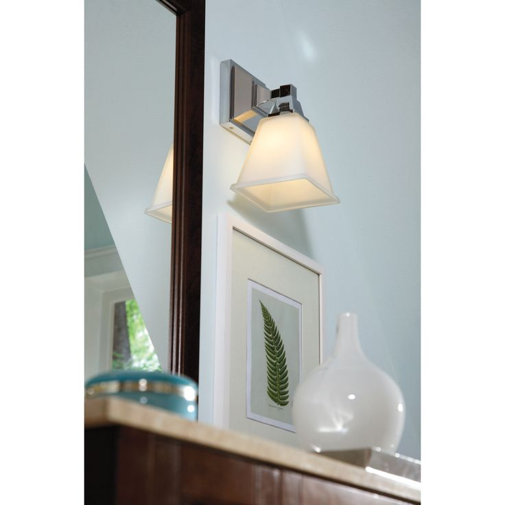 A white shade gives the Denhelm light a clean, white finishing touch that will brighten any home space. Available in three modern colors, this one-light wall sconce is safety listed for use in damp locations, making it perfect for a bathroom space.