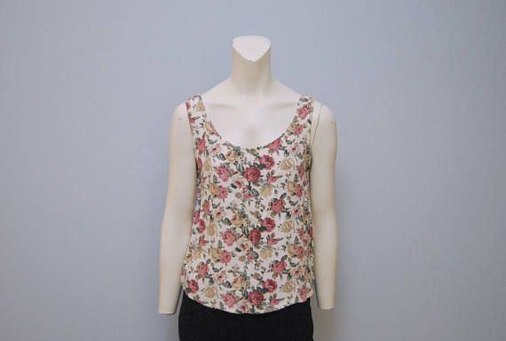 Vintage 1990s tank top with a great floral print! Brand is rampage. Size is small. Curved hem that is longer in the front than on the sides. Has slight discoloration by the collar (shown in the close up photo), but otherwise in excellent condition!  Measurements (taken when laid flat): Armpit-Armpit: 18 Length (at longest part of curved hem): 23