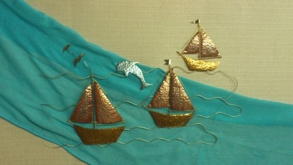 three sailboats travelling with a dolphin in a Greek sea