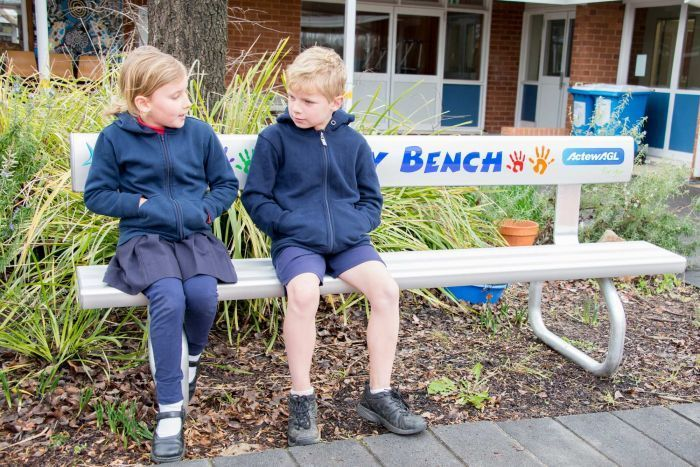 Student asking another student sitting on a buddy bench to play - Buddy Bench helping Canberra primary school students combat loneliness in the playground