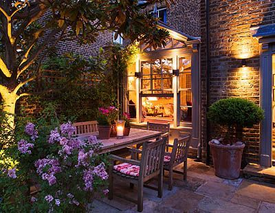 DESIGNER BUTTER WAKEFIELD, LONDON : A PLACE TO SIT - THE YORK STONE TERRACE AT NIGHT WITH WOODEN TABLE AND CHAIRS ON PATIO AND CONSERVATORY BEHIND - LIGHTING