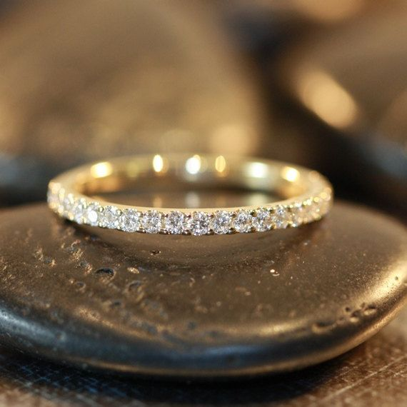 This 14k yellow gold petite pave set diamond wedding band features sparkling conflict free diamonds set half circle of the ring and is finished with