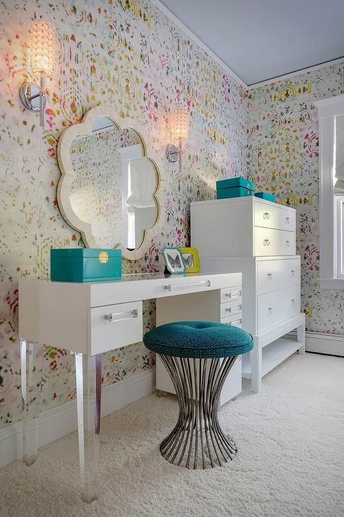 Chic teen girl's bedroom features walls clad in Kandy Brit Pop Wallpaper lined with a white vanity adorned with lucite pulls and lucite legs paired with a turquoise Greek key stool under a cream scalloped mirror, Made Goods Fiona Mirror, next to a Bungalow 5 Pandora Tall 4 Drawer.