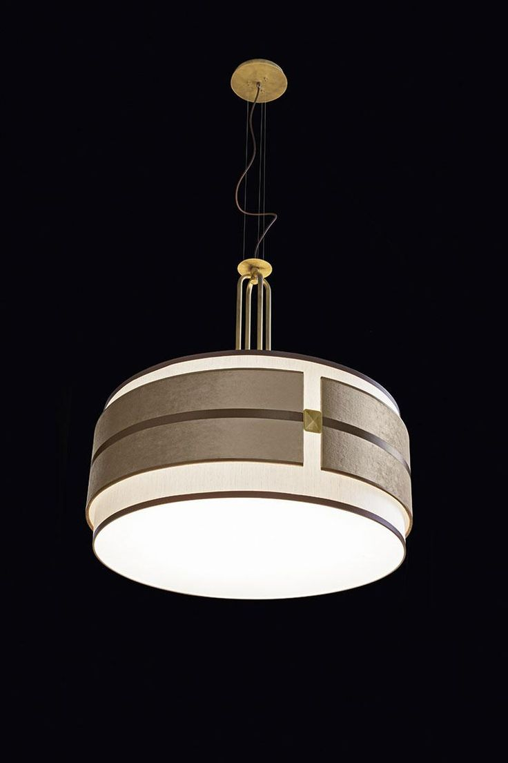 "Tamburo lighting collection by Oasis is a basic, simple shape of a white sand cotton cylinder enclosing the light – fashionably reinterpreted by adding a chic horizontal ring of decorative elements – this is what makes ""Tamburo"" stand out and impress. Antique gold finishings and studs, velvet and dark brown satin elements and a velvet grosgrain ribbon play with the light and their own reflections to create an ambient rich in emotions and content."
