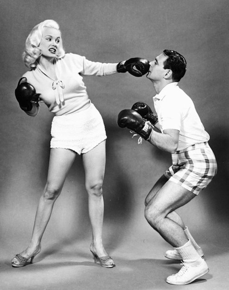 In this oddly-posed photo from the 1950's, actress Mamie Van Doren punches her husband Ray Anthony in the nose.