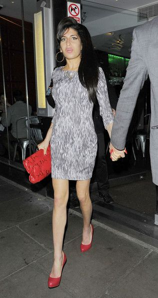 Amy Winehouse Photos Photos - Amy Winehouse struggles to get into the backseat of a car as she and boyfriend Reg Traviss leave Ballans Restaurant in London. - Amy Winehouse at Ballans Restaurant