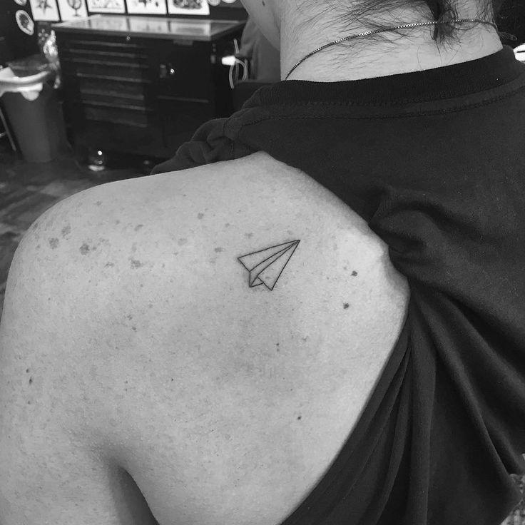 Tatuaje de avión de papel en la espalda.