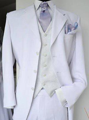 Traje de novio blanco con chaleco drapeado color crema y detalles en color lavanda