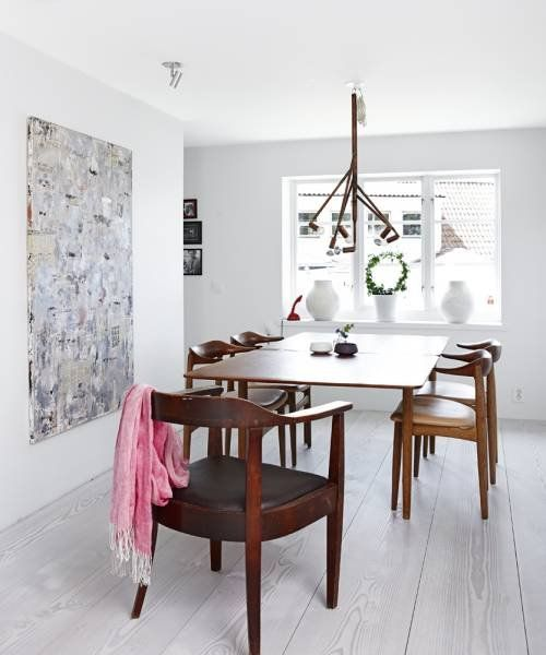 Classically Swedish, the dining room has white-washed floors and vintage Danish furniture.