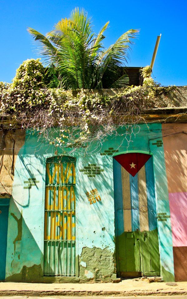 Colourful house with Cuban flag painted on it along with the Viva Cuba Libre slogan - a reminder of the Cuban revolution. | Honeymoons to the Caribbean http://www.pinterest.com/FLDesignerGuide/honeymoons-to-the-caribbean/