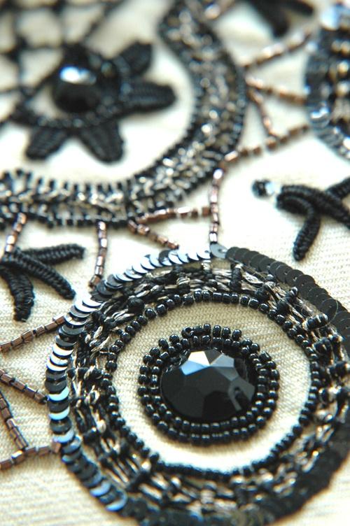 Creación con formas. piedras, mostacillas, canutillos en tonos negros.