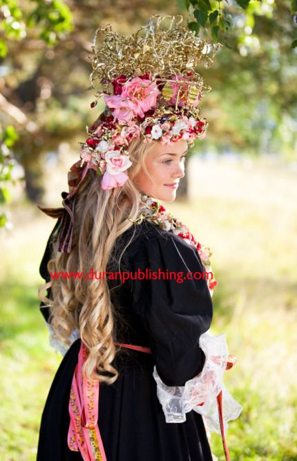 """Järvsö bride. """"The bridal crown, which is one of the most spectacular in Sweden, is decorated with flowers and silk ribbons. Around the sleeves there are white lace tied with floral silk ribbons. The bib, like the crown, is covered with flowers, pearls and curled strips made of thin sheets of brass"""" - Laila Durán,"""