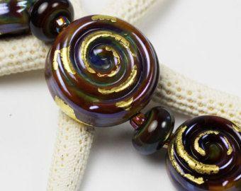 Ce nouvel ensemble de 9 perles de verre au chalumeau à la main est fait avec un verre gris transparent, accentué avec les tourbillons d'Ivoire et gris au fil d'argent fin, parsemée de noir et clair, le dépoli pour un mat finition. Cette forme est parfaite pour les colliers!  * Mesures: Focales sont de 27 à 30mm, trou à, perles d'accent sont de 15mm. * Taille mandrin : 3/32 po  Mes perles de verre de Murano sont fabriqués dans mon atelier du Nord-Ouest du Pacifique et sont four de recui...