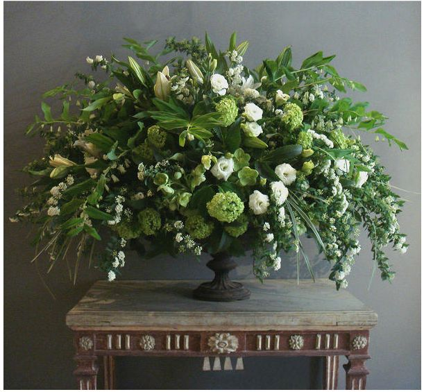 A late spring garden arrangement of spirea, viburnum, lilies, variegated liriope, lisianthus, green hellebores, and Solomon's Seal, in a 19th-century French cast-iron urn. L. Becker Flowers