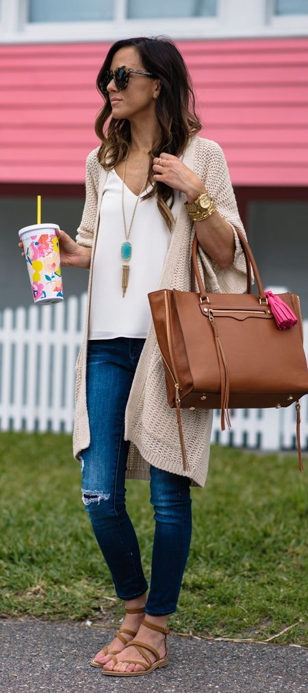 Spring fashion inspiration. Blue jeans, white blouse and camel cardigan. Brown leather handbag.