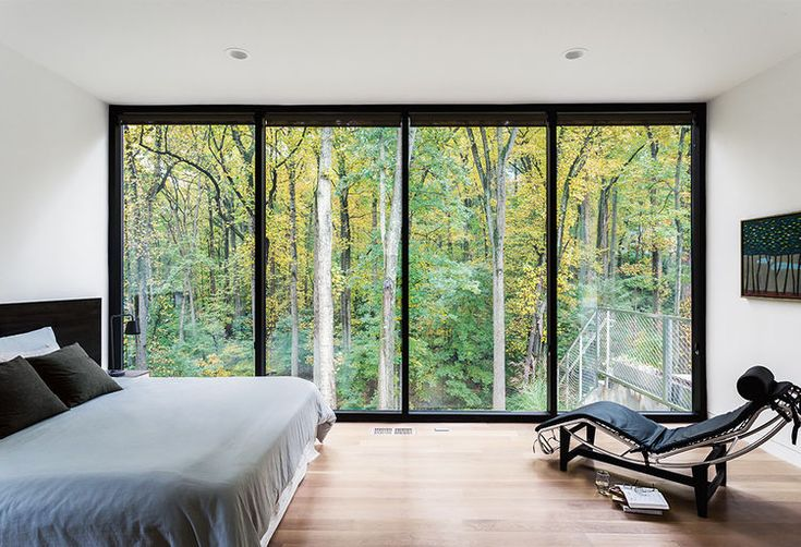 Black windows frame forest view, with Corbusier LC4 chair.