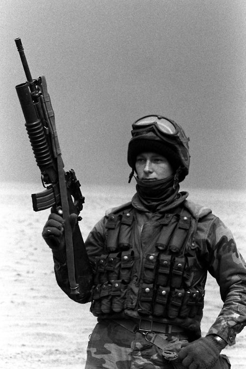Wearing a grenadier's vest filled with 40mm grenade cartridges, Lance CPL. Charles E. Blevins stands watch on the perimeter of a desert camp site following the withdrawal of Iraqi troops from Kuwait during Operation Desert Storm. Blevins is armed with an M-16A2 rifle equipped with an M-203 grenade launcher, 02/01/1991