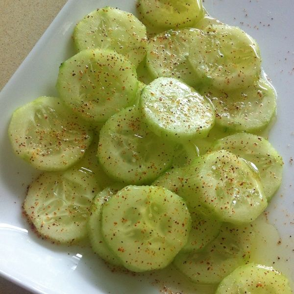 Sliced cucumber, lemon juice, & olive oil, with salt, pepper, & chili powder on top