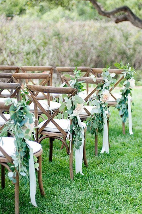 Unas ramas con cintas en color crema para una decoración sencilla del pasillo central de la ceremonia de boda. Fotografia Angie Silvy Photography.