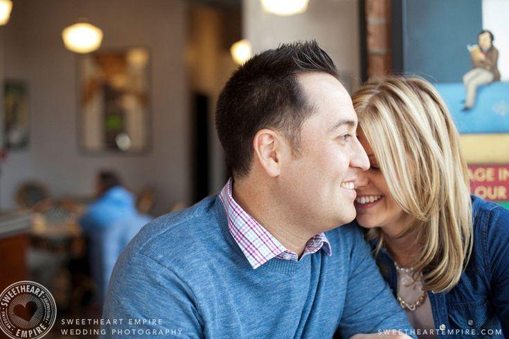 Cute couple snuggling in a cafe. Coffee shop engagement photos, Toronto Balzac's Liberty Village. #sweetheartempirephotography