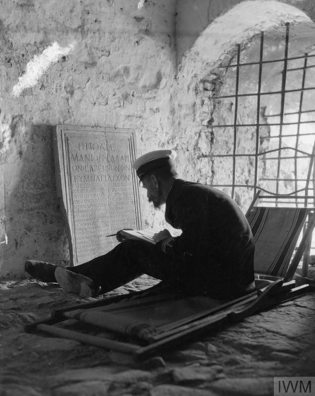 WWI, British forces in the Salonika campaign, 1916. Lt. Comm. Ernist Gardiner seen in the White Tower on the water front of Salonika, working on an ancient marble memorial plaque praising Sabinus for his benefactions. ©IWM