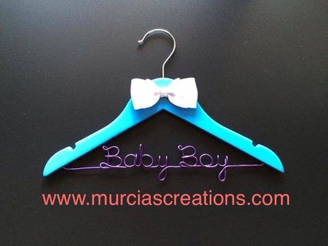 Coat Hanger Lovely handmade blue hanger with wording in purple wire and white ribbon. The perfect gift idea for baby showers and newborns. $20. Aud.