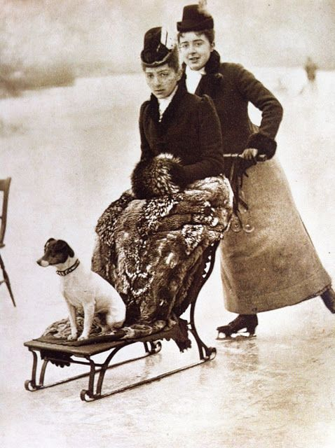 1880s Victorian ice skating outfits, with long skirts, high collars, nipped-in waists, chic little hats, and fur muff. An alert and elegant little dog makes a finishing fashion touch. Photo by H. Stevens. Copyright: British Library Board.