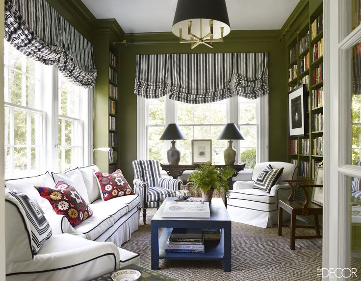 In the small sitting room of a Nashville home, the sunroom's sofa and armchairs are upholstered in a canvas duck. The Regency library chair is covered in the same Quadrille cotton stripe as the Roman shades.