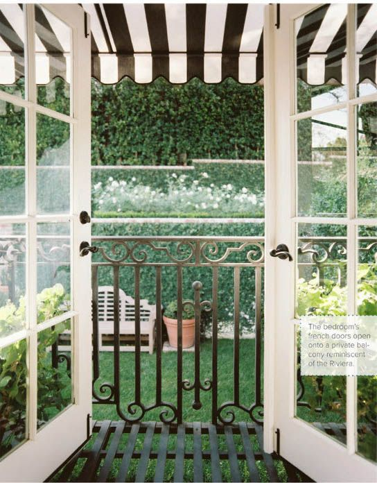 french doors under a black-and-white-striped awning open onto a garden