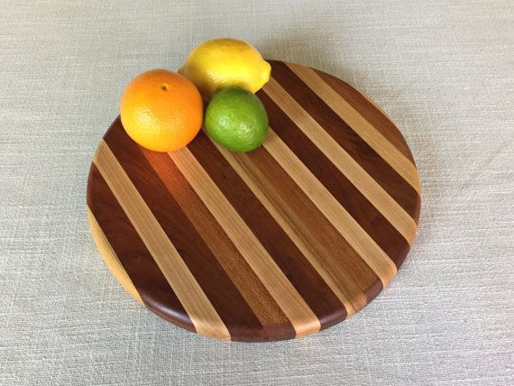 This circle shaped cutting board is hand crafted from various hardwoods including hickory, maple, cherry, and mahogany. These contemporary cutting boards are designed and meticulously handmade by cutting, gluing and clamping strips of various hardwoods. They are then cut to shape, sanded and finished with many coats of Howard butcher block and cutting board oil to establish and maintain a natural beauty and glow to the wood. I suggest using butcher block and cutting board oil to maintain…