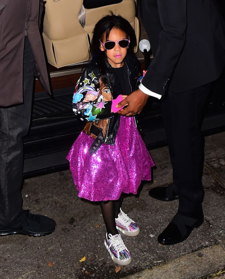 Mother like daughter? Blue Ivy clutches a toy microphone as she steps out of car