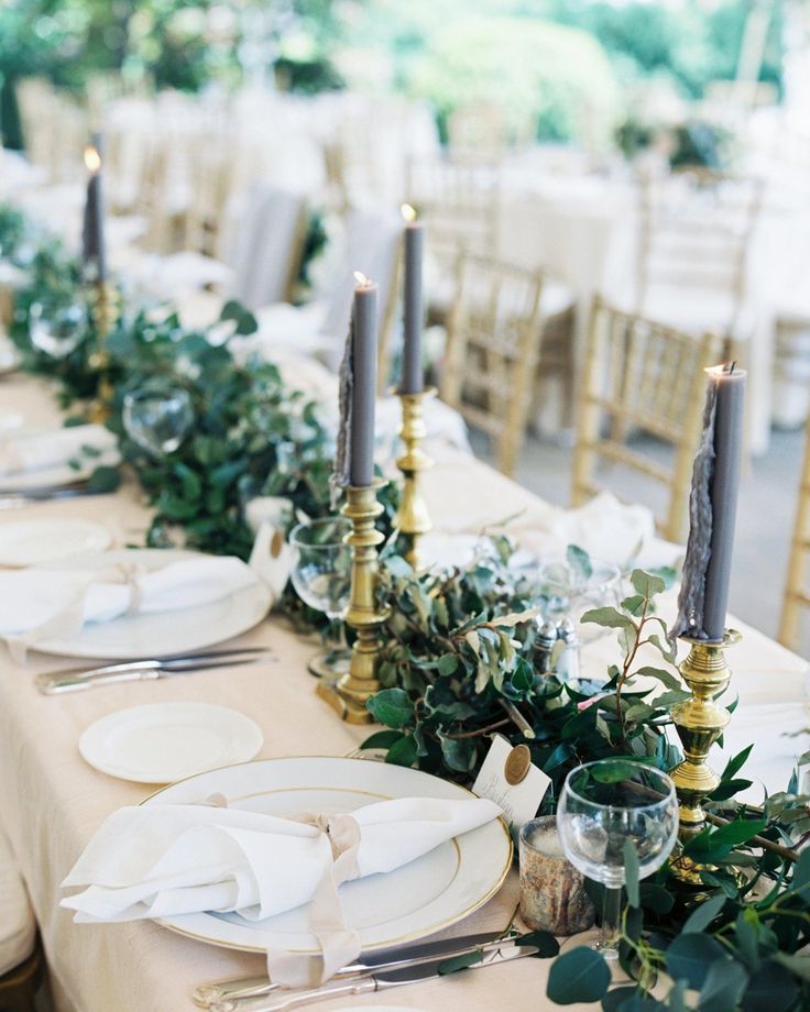 "A Dreamy Garden Wedding in Nashville, Tennessee | Martha Stewart Weddings - The table décor was kept neutral with greenery arranged along the cream linens. ""The brass candlesticks were from my mother and grandmother,"" says the bride. ""Each year we gift each other more at Christmas."" Along with taller, gray candles were smaller white ones in mercury glass votive holders."